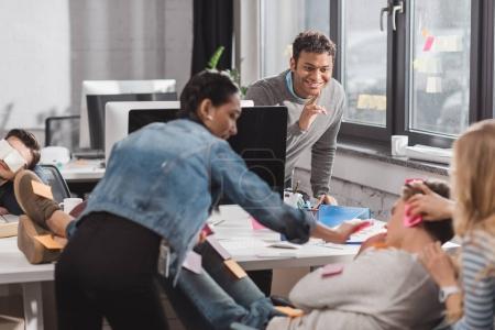 people having fun in office, women glue stickers on man