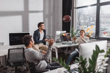Men playing with ball in modern office