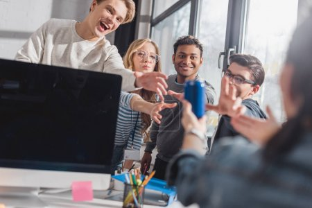 people reach hands for bank with drink in office