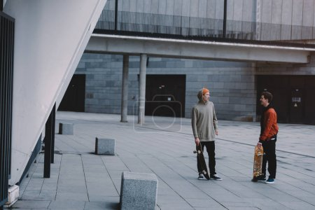 skateboarders talking after ride in modern urban location
