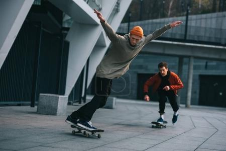 handsome young men riding skateboards in urban location