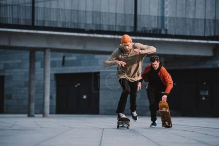 stylish young men in streetwear outfit riding skateboards
