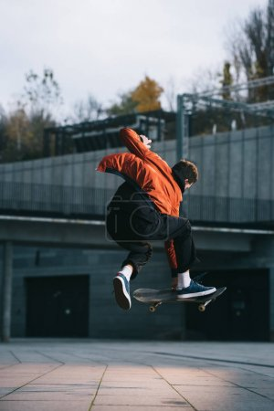 skateboarder in red jacket performing jump trick in urban location