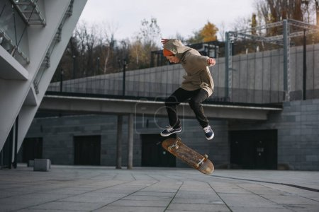 skateboarder in streetwear outfit performing jump trick in urban location