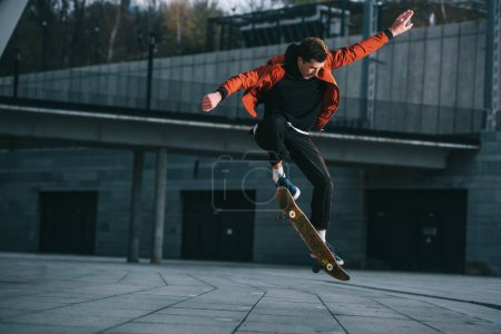 Photo for Skateboarder doing jump trick in urban location - Royalty Free Image