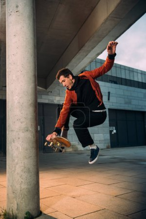 stylish young skateboarder performing jump trick in urban location