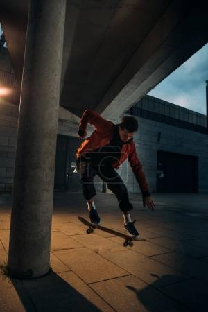 skateboarder performing jump trick in urban location at evening