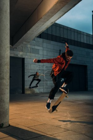 skateboarders performing jump tricks together at urban location