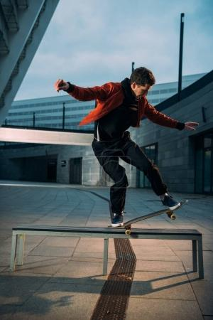 young skateboarder performing trick on bench