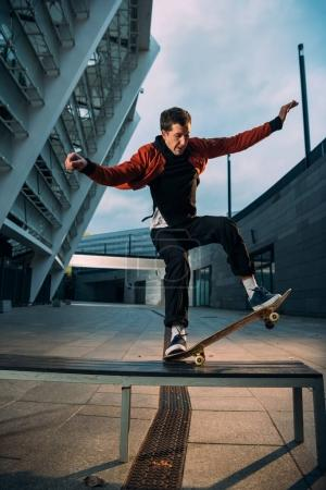 young skateboarder in stylish outfit balancing with board on bench