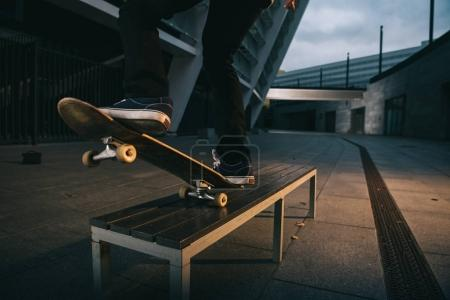 cropped shot of skateboarder balancing with board on bench