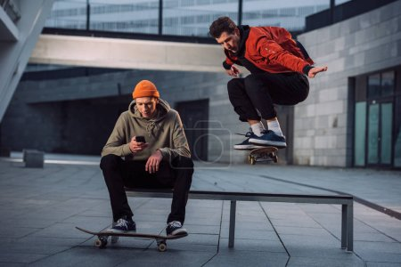skateboarder jumping over bench while his partner sitting on it and using phone