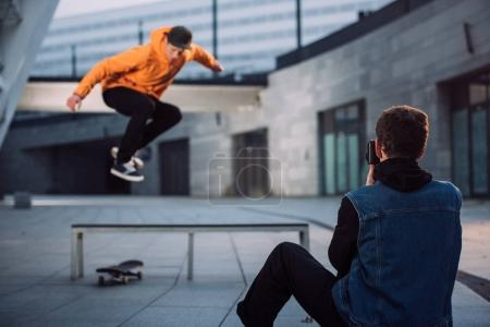 man taking photo of skateboarder jumping over bench