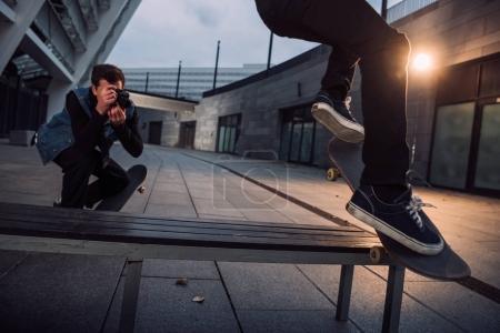 close-up shot of man taking photo of skateboarder doing trick