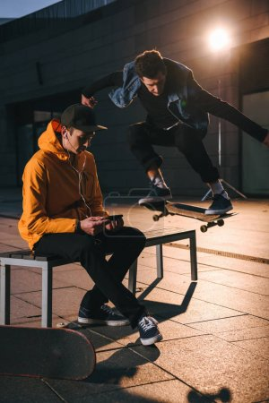 skateboarder jumping over bench while man sitting on it and listening music