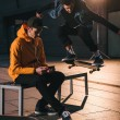 Skateboarder jumping over bench while man sitting ...