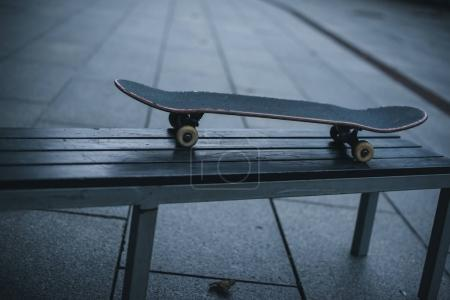 vieille de skateboard debout sur l'extérieur du banc