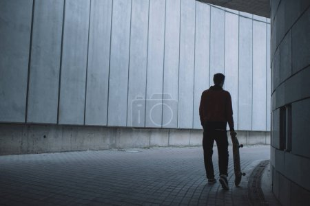 skateboarder standing with board in front of grey concrete wall