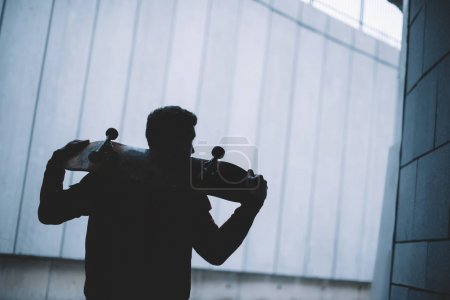 young skateboarder standing with board on shoulders in front of grey concrete wall