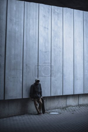 skateboarder with board leaning back on grey concrete wall