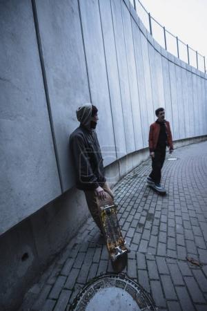 Photo pour Jeunes skateurs professionnels en tenue rue, passer du temps dans le paysage urbain - image libre de droit
