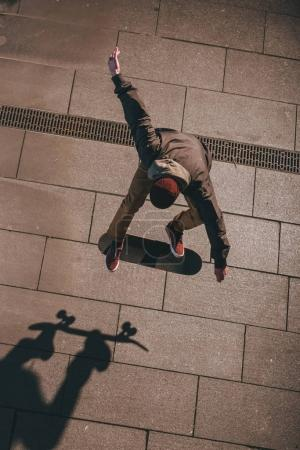 high angle view of skateboarder in modern streetwear performing trick