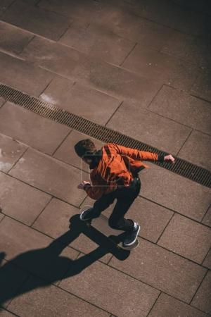 Photo pour Vue grand angle du skateboarder en veste rouge se préparant pour le tour - image libre de droit