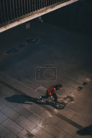 high angle view of skateboarder riding outdoors at late night