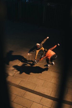 high angle view of skateboarders doing same trick together