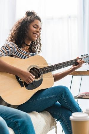 african american girl playing acoustic guitar