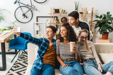 Photo for Happy multiethnic teenagers sitting on sofa and taking selfie with smartphone - Royalty Free Image