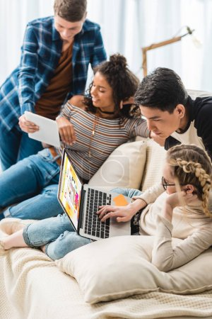 smiling multicultural teenagers looking at laptop with loaded website