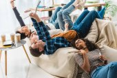teens lying on sofa and taking selfie with tablet and smartphone
