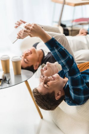 Photo for Caucasian teenagers lying on sofa and taking selfie with tablet and smartphone - Royalty Free Image