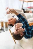 adolescents Caucasiens couché sur le canapé et prise selfie avec tablette et smartphone