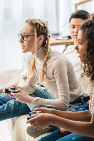 multiethnic girls playing video game at home