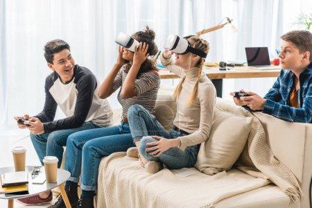 Photo pour Adolescentes multiculturelles excitées je regarde quelque chose avec les casques de réalité virtuelle - image libre de droit