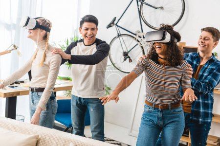 laughing boys holding multicultural girls watching something with virtual reality headsets
