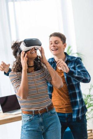 Foto de Chica adolescente afroamericana emocionada viendo algo con casco de realidad virtual - Imagen libre de derechos