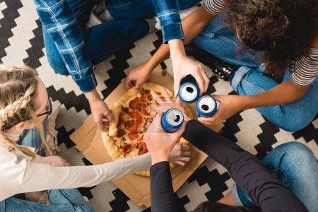 Photo pour Image recadrée d'adolescents cliquetant avec des canettes et prenant de la pizza - image libre de droit