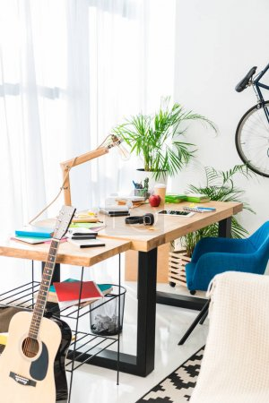 working table and acoustic guitar at home