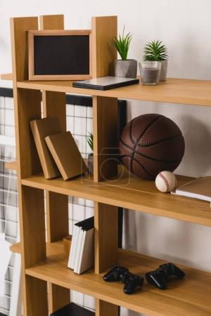 Basketball and baseball balls on shelves