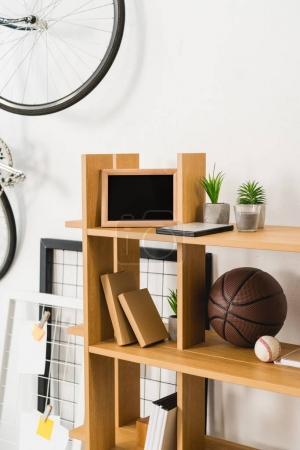 Bike on wall and basketball and baseball balls on shelves