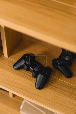 overhead view of two game pads on wooden shelves