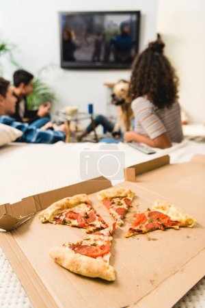 multicultural teens playing video game with pizza on foreground