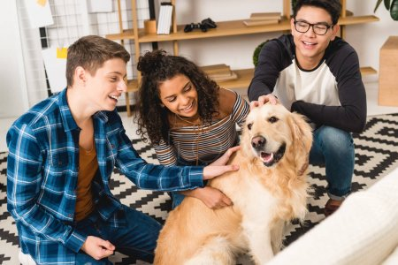 happy multiethnic teens palming dog at home