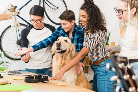 smiling multicultural teenagers showing something on laptop to dog