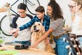 souriant multiculturelles adolescents montrant quelque chose sur l'ordinateur portable pour chien