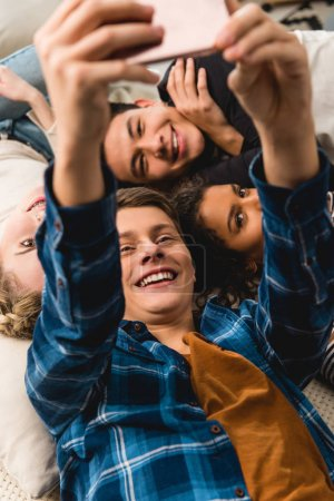 overhead view of multicultural teens taking selfie while lying on bed