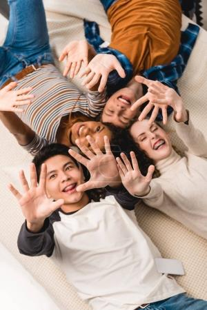 overhead view of smiling multiethnic teens waving hands